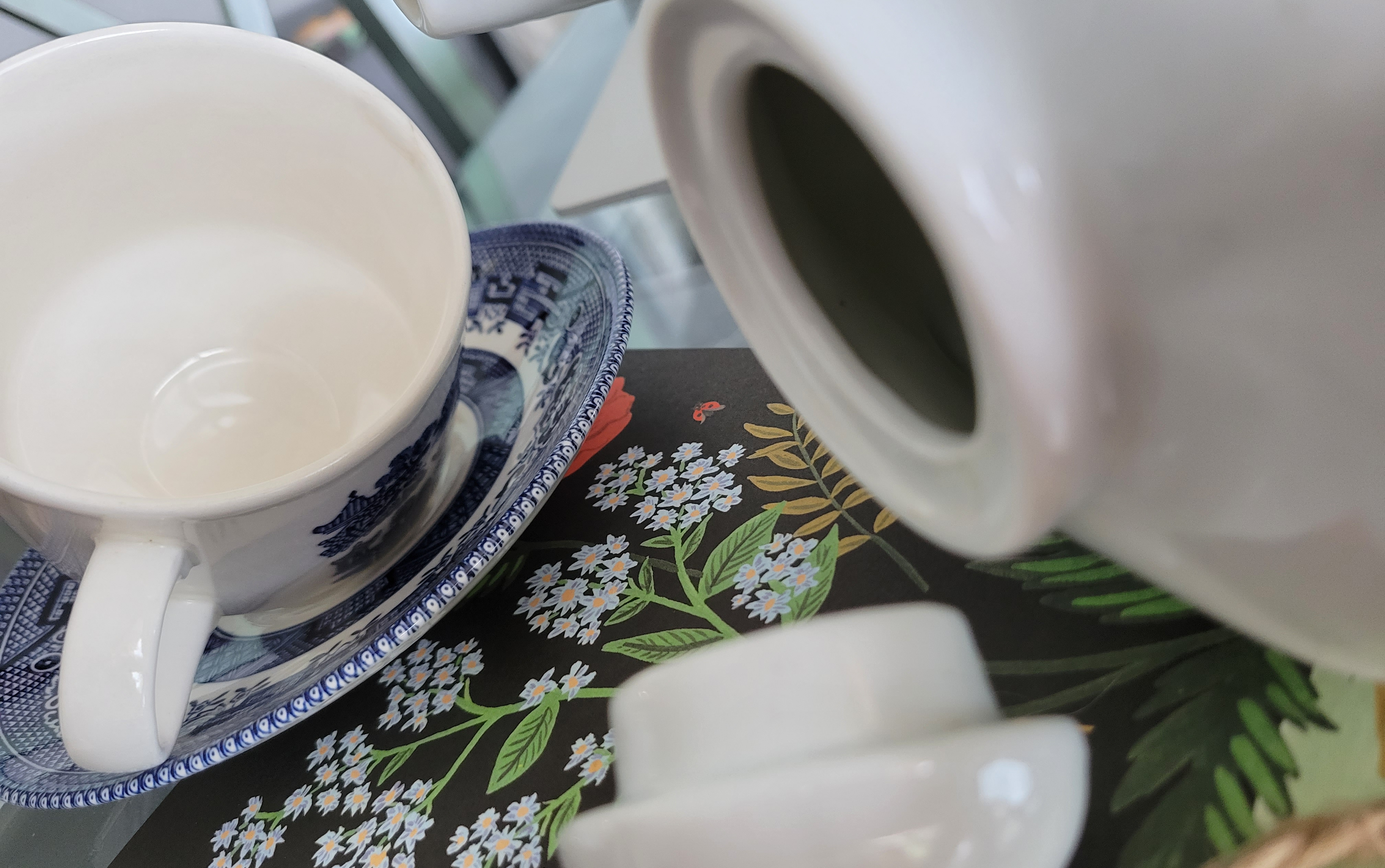 A tilted tea cup and a turned over teapot, the lid lying on a a piece of floral stationary on a glass table.